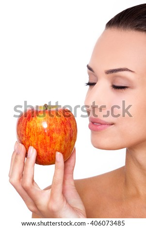 Fruit is the best snack. Cropped shot of attractive young woman holding an apple in hand with closed eyes against white isolated background - stock photo