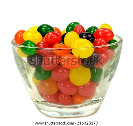 Fruit jelly beans in many colors in a glass bowl on a white background.