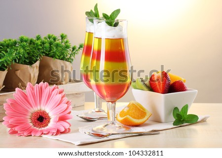 fruit jelly in glasses and fruits on table in cafe