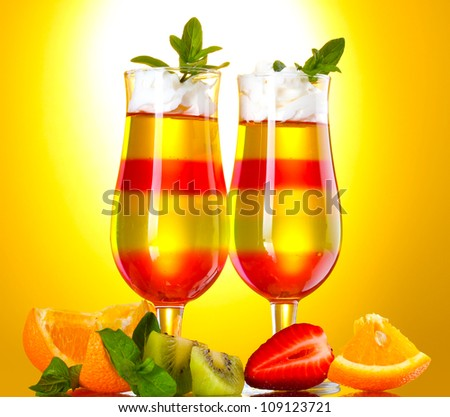 fruit jelly in glasses and fruits on yellow background - stock photo