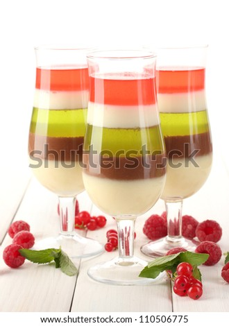 fruit jelly in glasses, berries and mint on wooden table