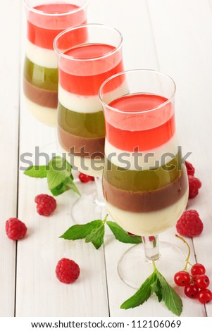 fruit jelly in glasses, berries and mint on wooden table - stock photo