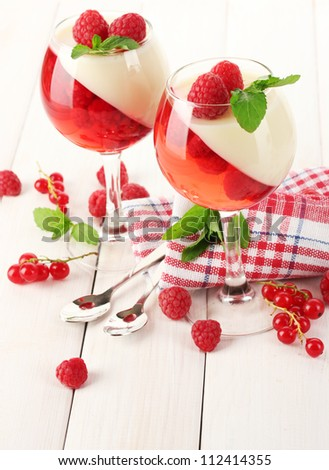fruit jelly with berries in glasses on wooden table