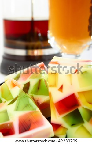 Fruit jelly with teapot and cup of tea macro - stock photo