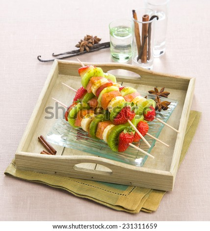 fruit kebabs on wooden skewers on a tray with spices anise vanilla cinnamon - stock photo