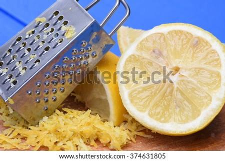 Fruit lemon fruit and lemon zest with grater on wooden board - stock photo