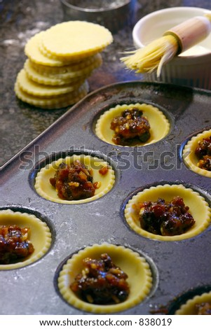 Fruit pies being prepared in a kitchen enviroment, with pastry tops and brush in the out-of-focus background.  Shallow DOF; Focus point it second pie down on the left. - stock photo