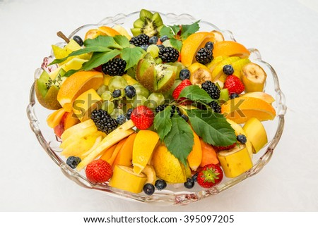 fruit plate and berries adorned with leaves, a plate with bananas, kiwi, grapes, strawberries, strawberries, blackberries decorated with leaves, tropical fruits in combination