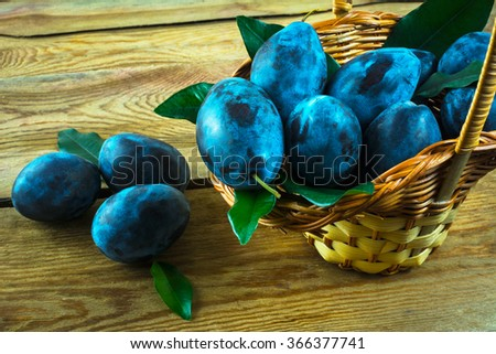 Fruit plum prunes in a basket on a wooden table, close up. Selective focus. Fruit. Fruits. Plum - stock photo