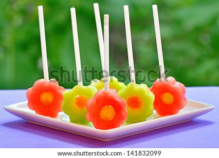 fruit pops of melon and watermelon on natural background - stock photo