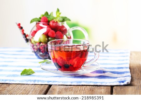 Fruit red tea with wild berries in glass cup, on wooden table, on bright background - stock photo