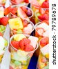 Fruit Salad arranged in plastic cups on a market stall focus on middle front cup. - stock photo