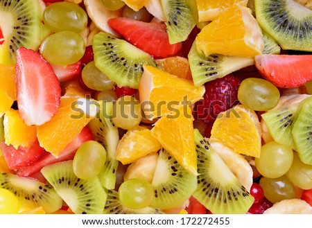 Fruit salad as background with strawberries, oranges and  kiwi. Top view