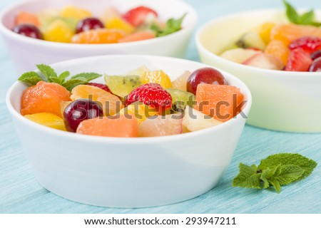 Fruit Salad - Bowls of fresh fruit salad on a blue background. - stock photo