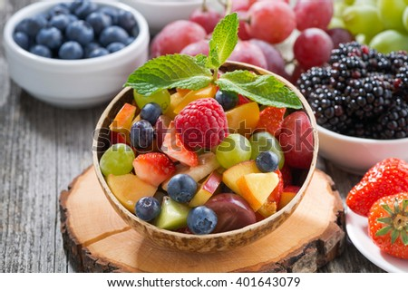 fruit salad in a bamboo bowl and fresh berries, close-up, horizontal