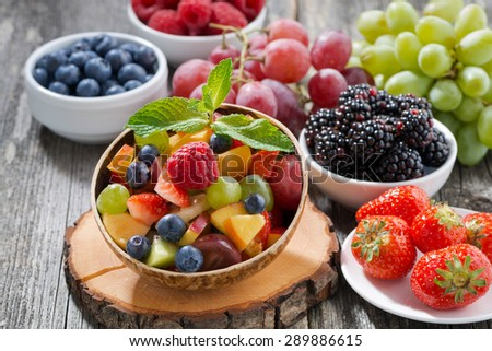 fruit salad in a bamboo bowl and fresh berries, horizontal - stock photo