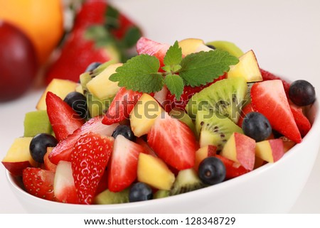 Fruit salad in a bowl with strawberries, kiwi, blueberries and peaches - stock photo