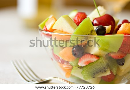 Fruit salad in a glass bowl, served on the table. Focus on blackberry. Natural light - stock photo
