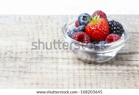 Fruit salad in small transparent bowl on wooden table. Copy space - stock photo