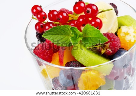 Fruit salad mix in glass on white background
