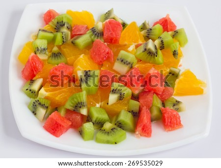 Fruit salad on white plate. Isolated on white.