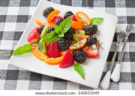 Fruit salad with fresh strawberries, blackberries,  kiwis and  kumquats on white plate. Healthy eating, berry dessert. selective focus. - stock photo