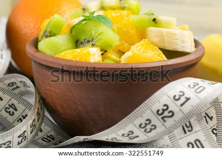 Fruit salad with kiwi, banana and orange for slimming and centimeter   - stock photo