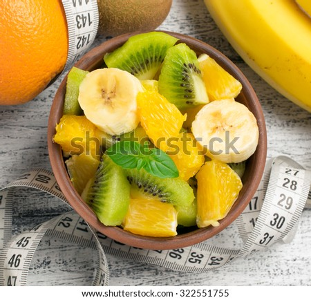 Fruit salad with kiwi, banana and orange for slimming and centimeter on the wooden board  - stock photo