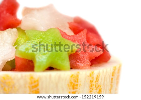 Fruit salad with melon, watermelon and kiwi stars in cantaloupe bowl, isolated on white - stock photo