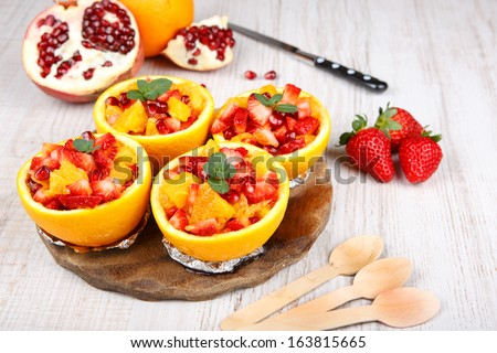 Fruit salad with pomegranate, strawberry and oranges in hollowed-out orange. On wooden table.