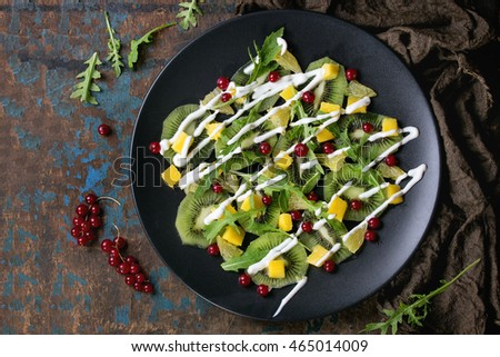 Fruit salad with sliced kiwi, mango, orange, red currant, rucola and yogurt dressing, on black plate with over dark wood textured background. Healthy eating theme. Top view