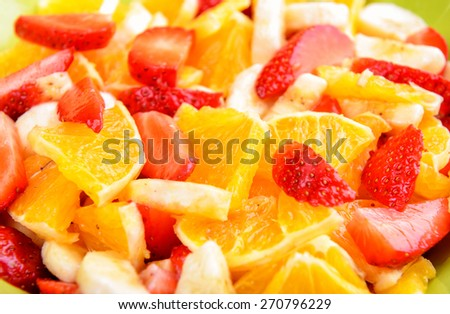 Fruit salad with strawberries, oranges and bananas - stock photo