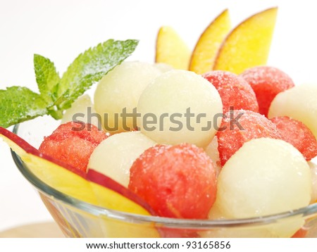 fruit salad with watermelon and melon balls. decorate with peach and mint - stock photo