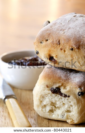 Fruit scones, with bowl of strawberry jam.  Shallow depth of field.