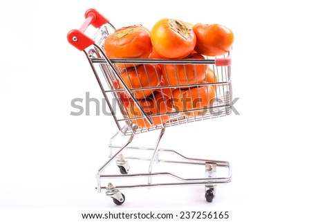 Fruit shopping. persimmon in shopping cart isolated over white background