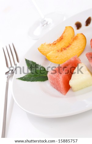 fruit slices on white plate and fork on the side