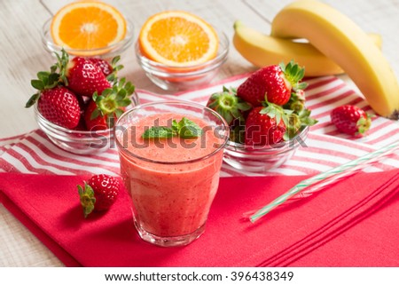 Fruit smoothie glass on red and white stripes napkins around spread ingredients: strawberries, sliced orange, bananas, blurred on white wood background. Strawberry orange banana smoothie. Horizontal.