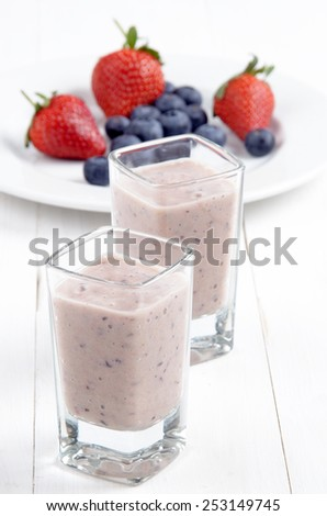 fruit smoothie in a shot glass made from strawberries, blueberries, banana, syrup and yogurt - stock photo