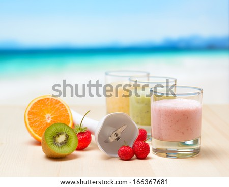 Fruit smoothie on wooden table on tropical beach. - stock photo