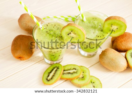 Fruit smoothie with fresh green kiwi on a wooden background