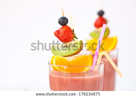 Fruit smoothies against a plain background - shallow dof - stock photo