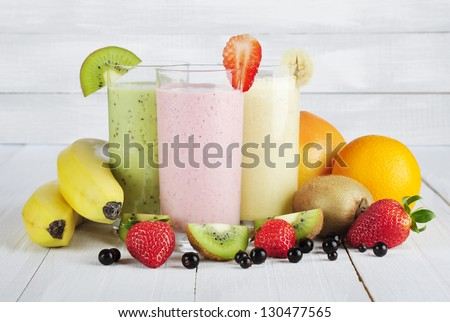 Fruit smoothies with black currant, strawberry, kiwi, orange and banana  on white wooden background - stock photo