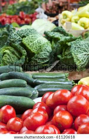Fruit stand in market with tomato, cucumber, zucchini, cabbage, bell pepper and more