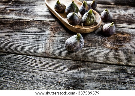 fruit still-life - above view of organic green and violet figs set on wooden tray on wood background for authentic texture effect - stock photo
