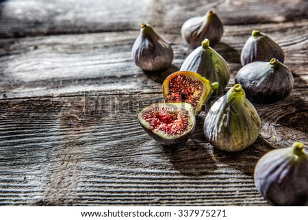 fruit still-life - closeup of several organic figs,whole and cut,on wood background for genuine texture effect and food freshness - stock photo
