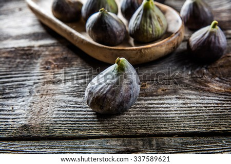 fruit still-life - group of organic green and violet figs set on wooden tray on wood background for authentic texture effect and food freshness - stock photo
