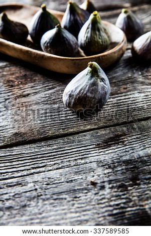 fruit still-life - tray of organic green and violet figs set on wooden tray on wood background for authentic contrast effect and food freshness, contrast effect - stock photo