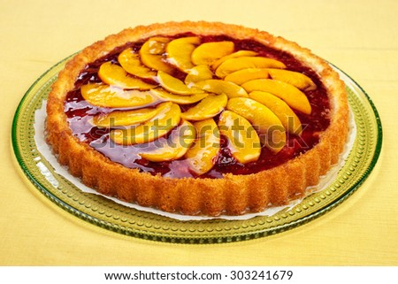 Fruit tart made from cherry jam and peach slices and juice with gelatin on top - stock photo