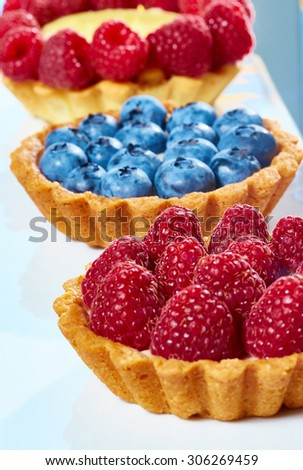 fruit tartlets with raspberries and blueberries. with copy space - stock photo