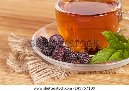 Fruit tea(tea package) in cup with blackberry - stock photo